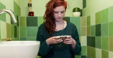 Woman with phone in the bathroom